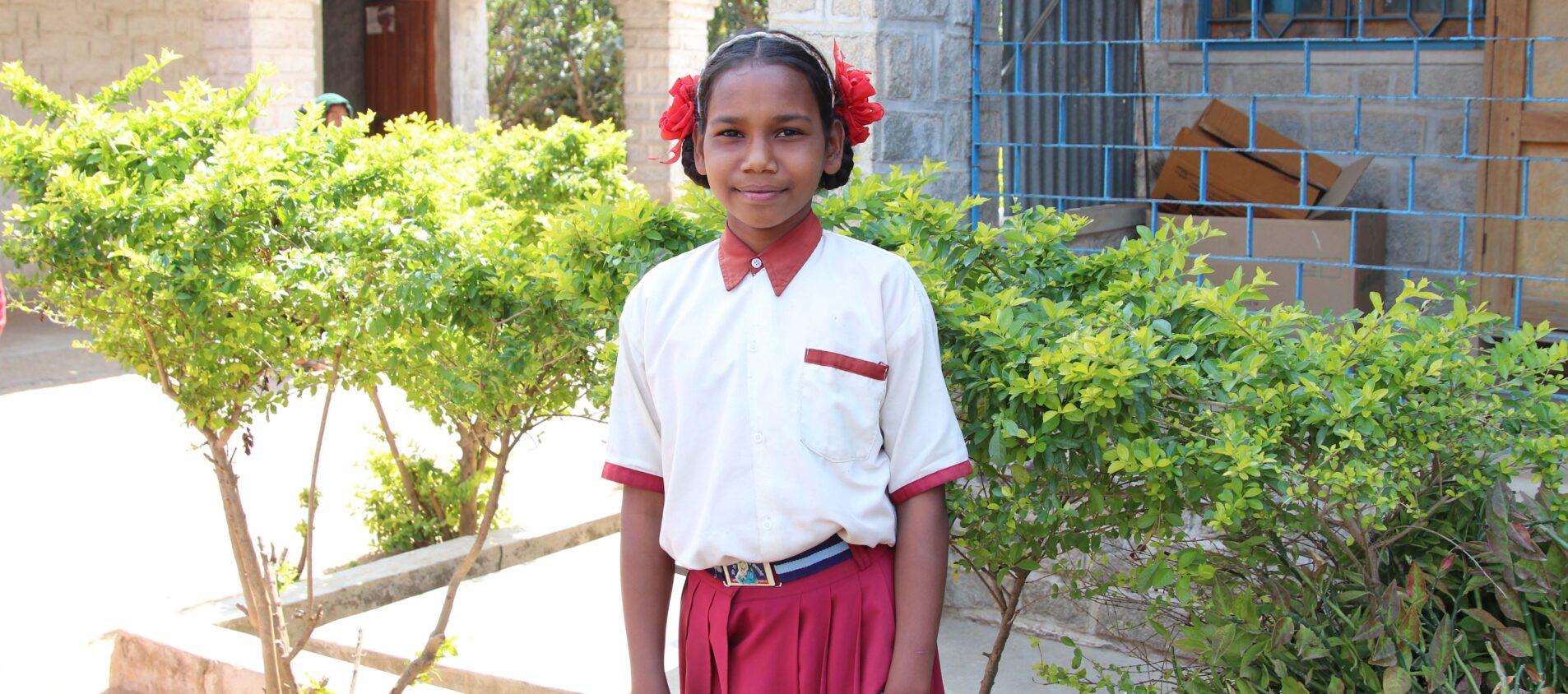 Flicka i skoluniform framför skolbyggnad i Indien.