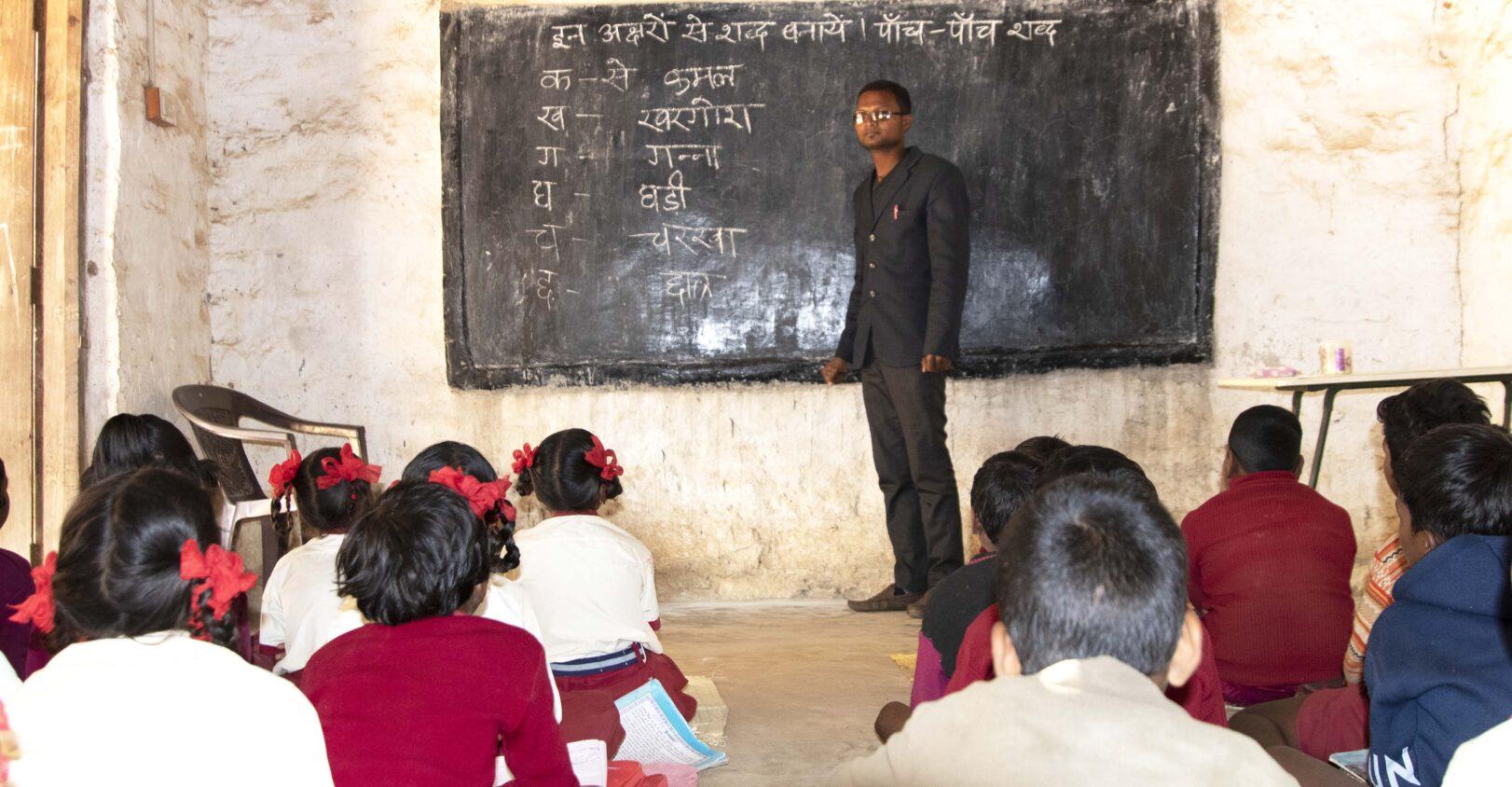 En man står framför svarttavlan och många elever sitter framför tavlan.