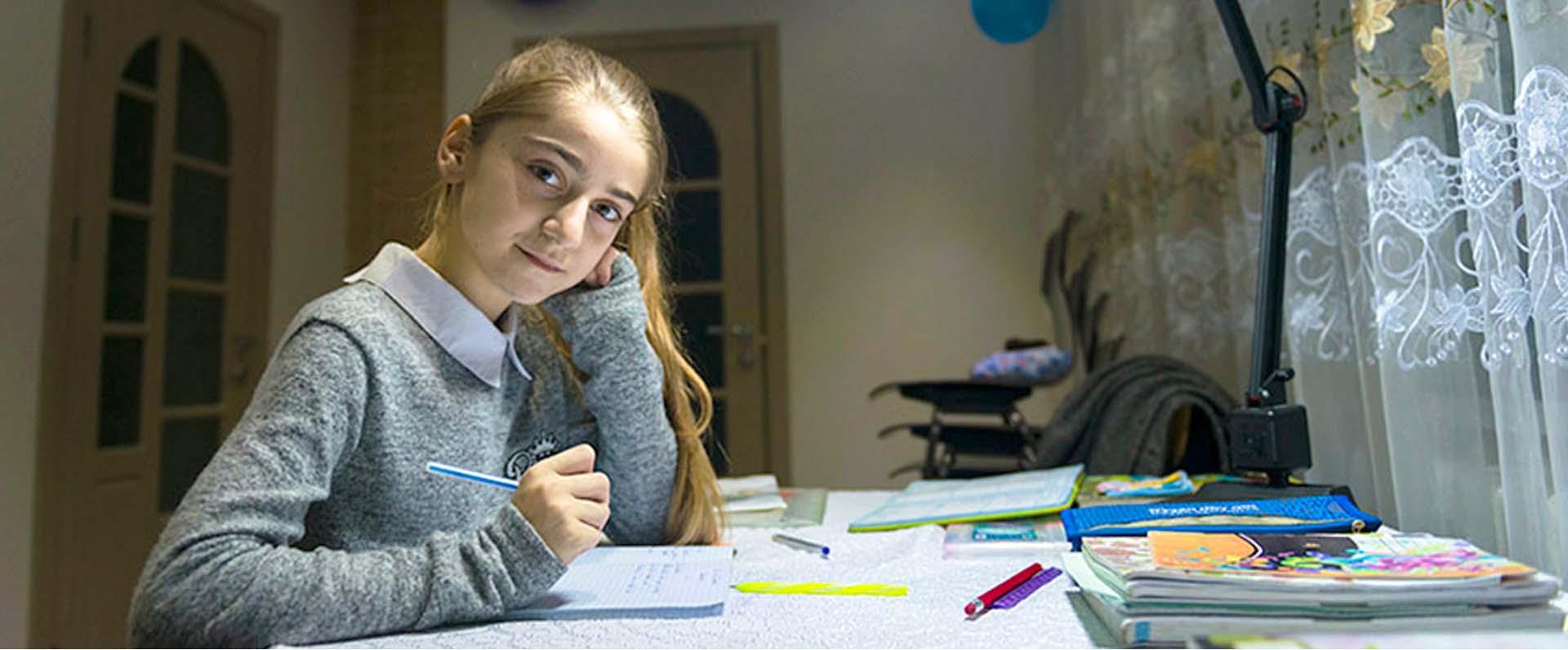 Porträtt av en flicka som sitter vid ett bord med skrivböcker framför sig.