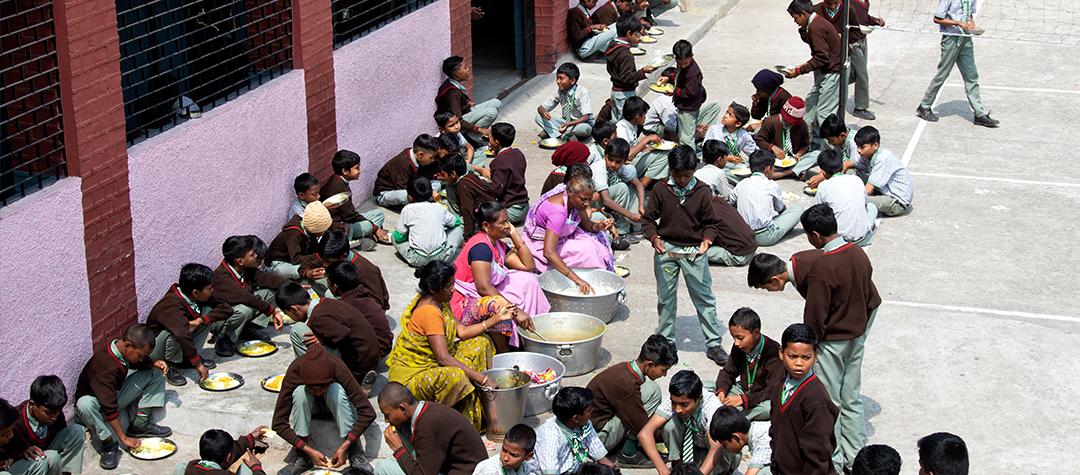 Elever i en skola i Indien äter skollunch på skolgården. På menyn står dahl med ris.