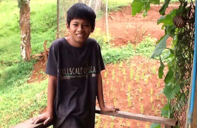 En pojke i skolålderna står framför en trädgård.