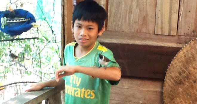 Pojke med fågel på handen.