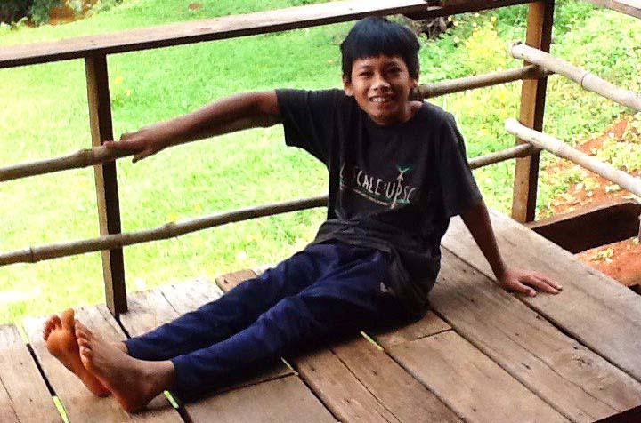 Pojke sitter på balkong, trädgård i bakgrunden.