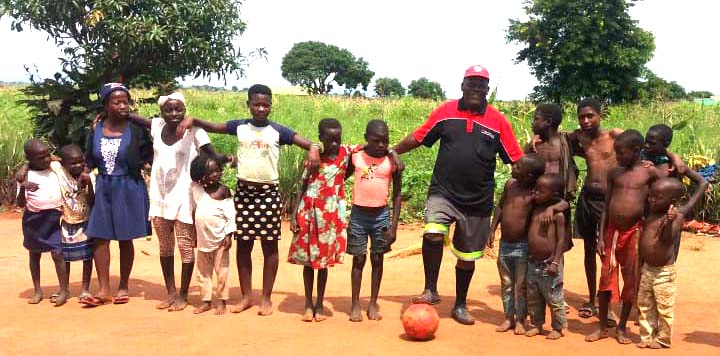Barn i olika åldrar står uppradade på en grusplan med en fotboll.