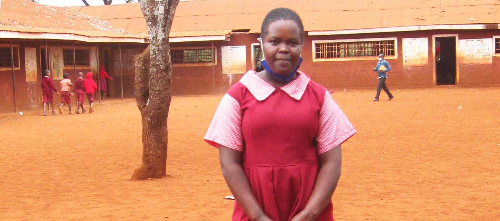 Flicka står på skolgård.
