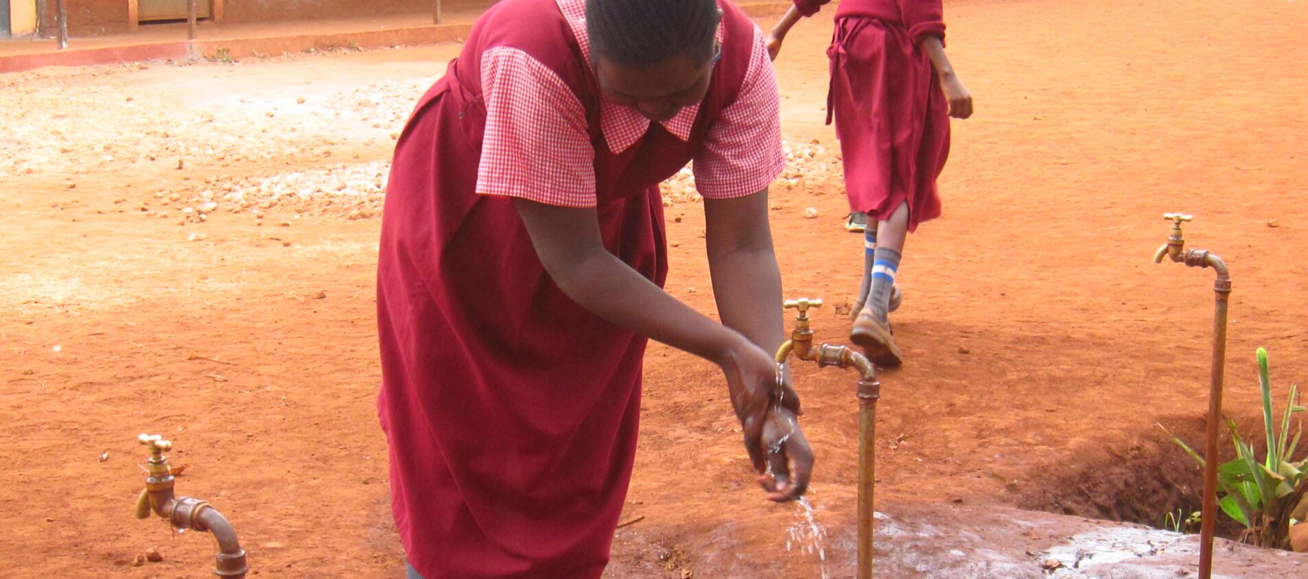 En flicka på en skolgård tvättar händerna under en kran.