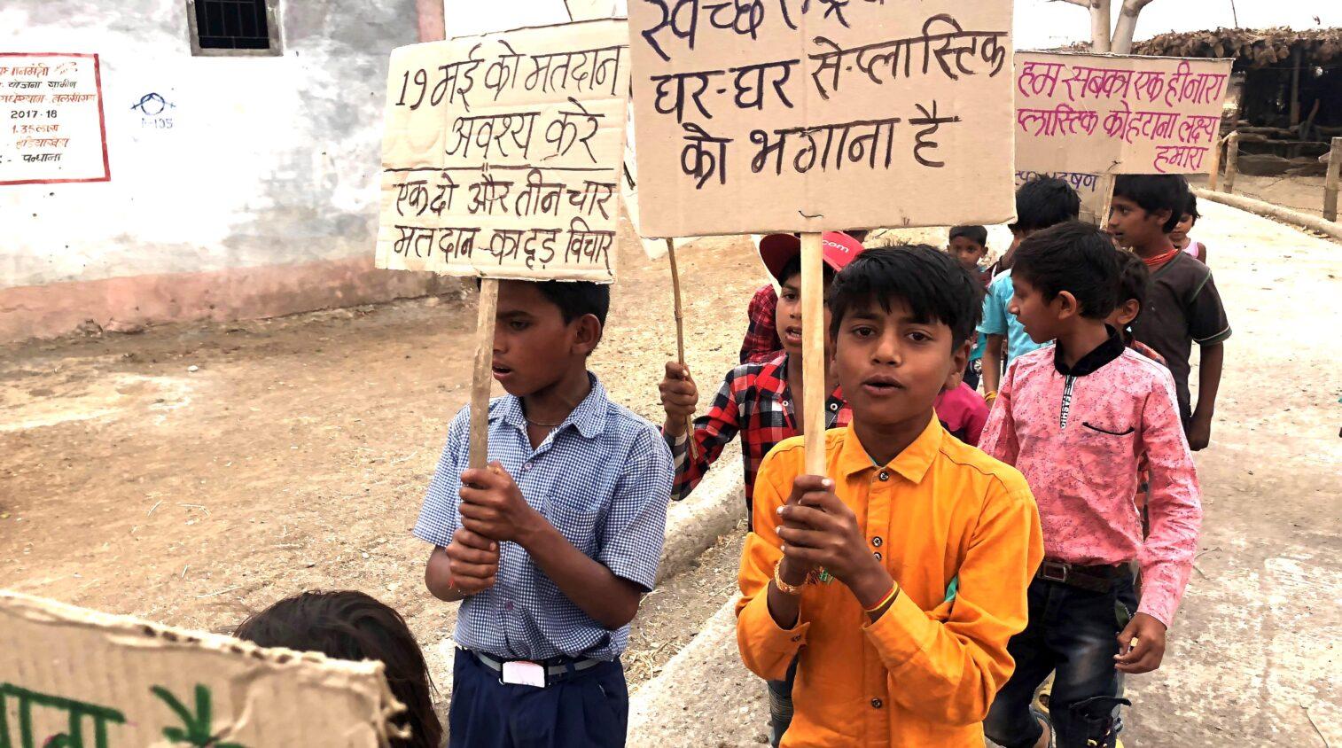 Barn som håller i plakat.