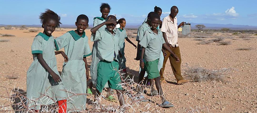 Medlemmar i barnklubben i Kurkum i Kenya på väg från skolan. Läraren är med.
