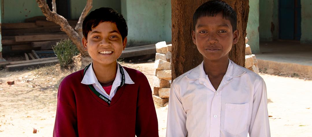 Dewraj (till vänster) och hans klasskamrater får ris och dhal till lunch i skolan