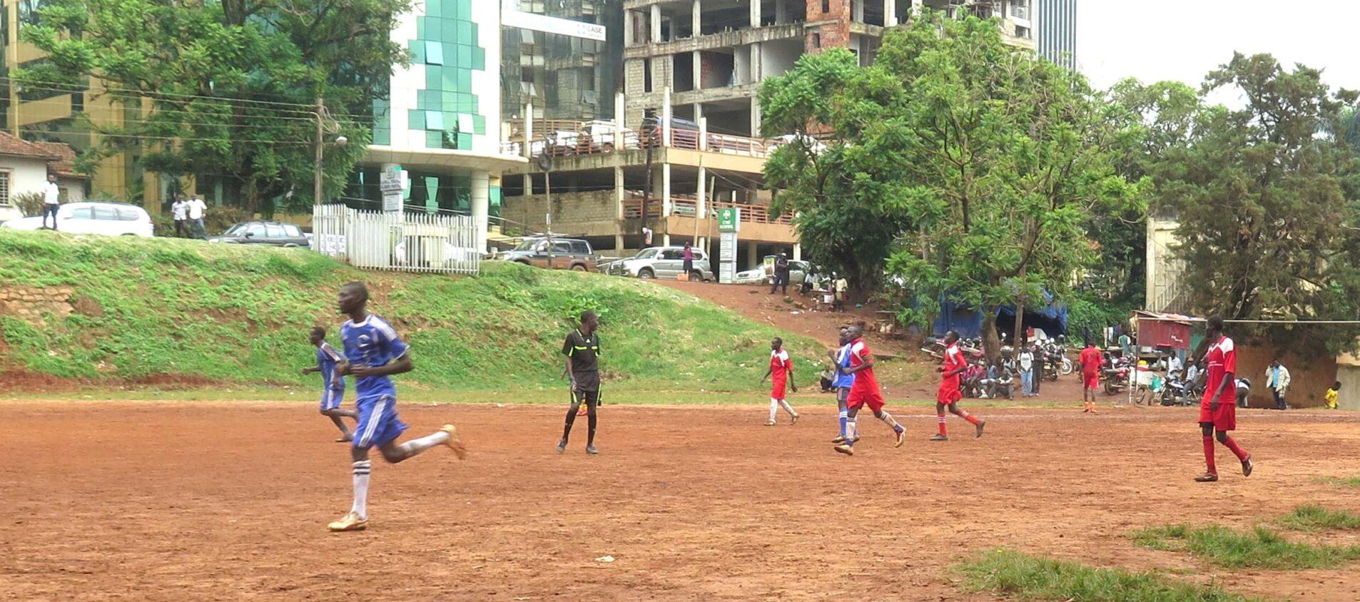 Ungdomar spelar fotboll på en stor grusplan. Höga hus i bakgrunden.