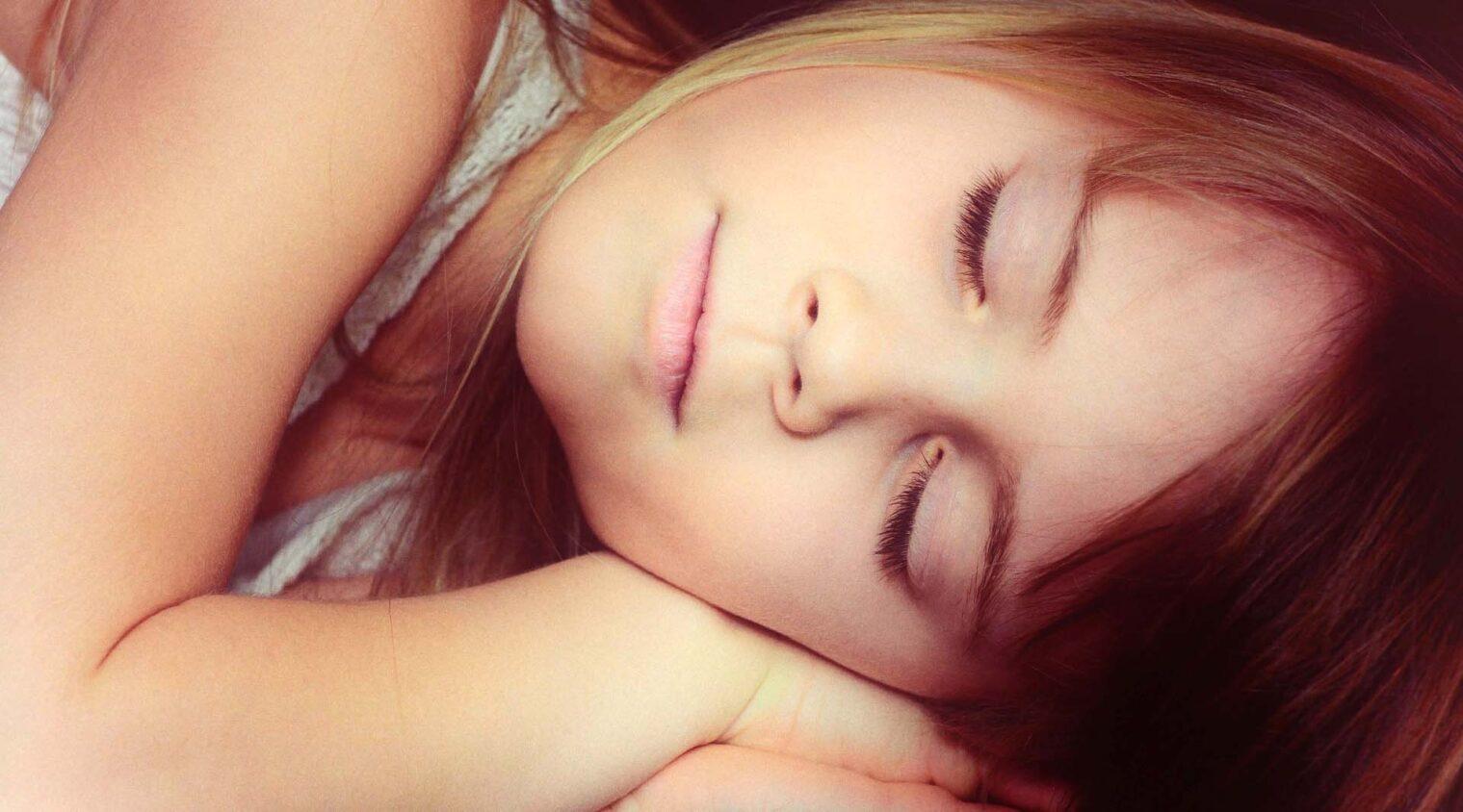 Ansikte på flicka med slutna ögon, händerna under kinden.