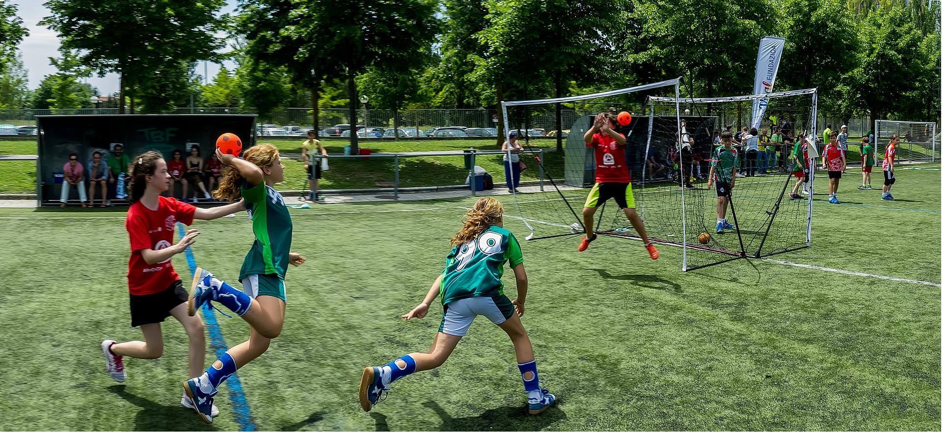 Tjejer spelar handboll på en gräsplan.