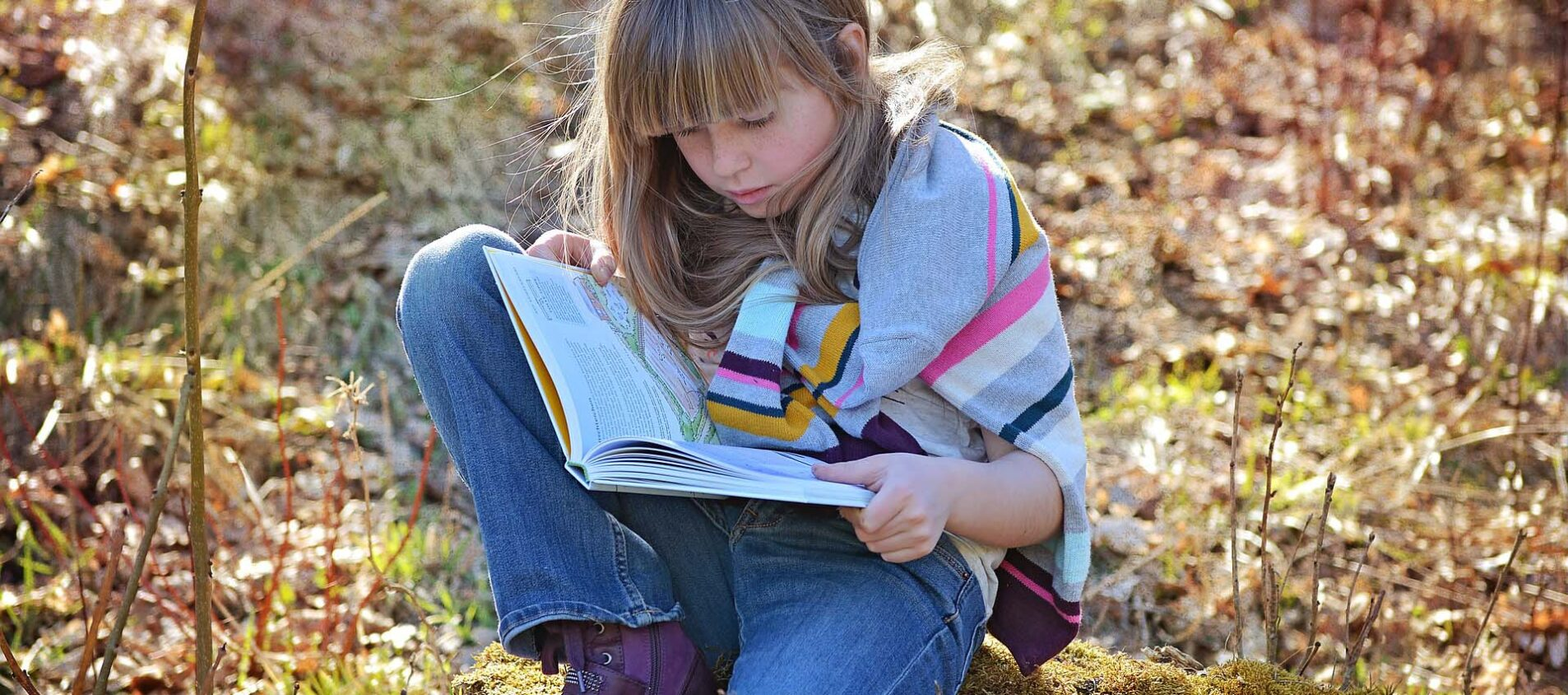Flicka sitter i naturen och läser en bok.