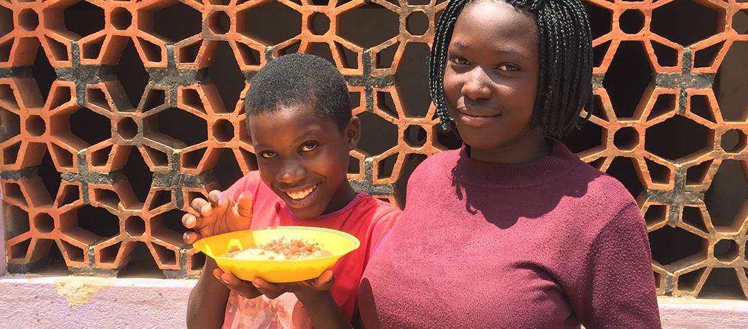 Julianah och hennes kompis Scovia har lunchrast från frisörutbildningen. På tallrikarna har de posho, ett majsmos som man äter med bönor.