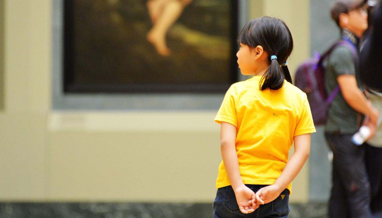 Flicka står framför en stor tavla på ett museum.