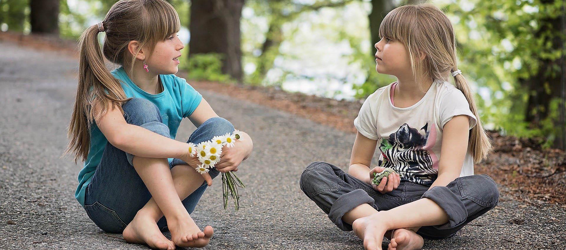 Två flickor som sitter på marken och pratar med varandra.