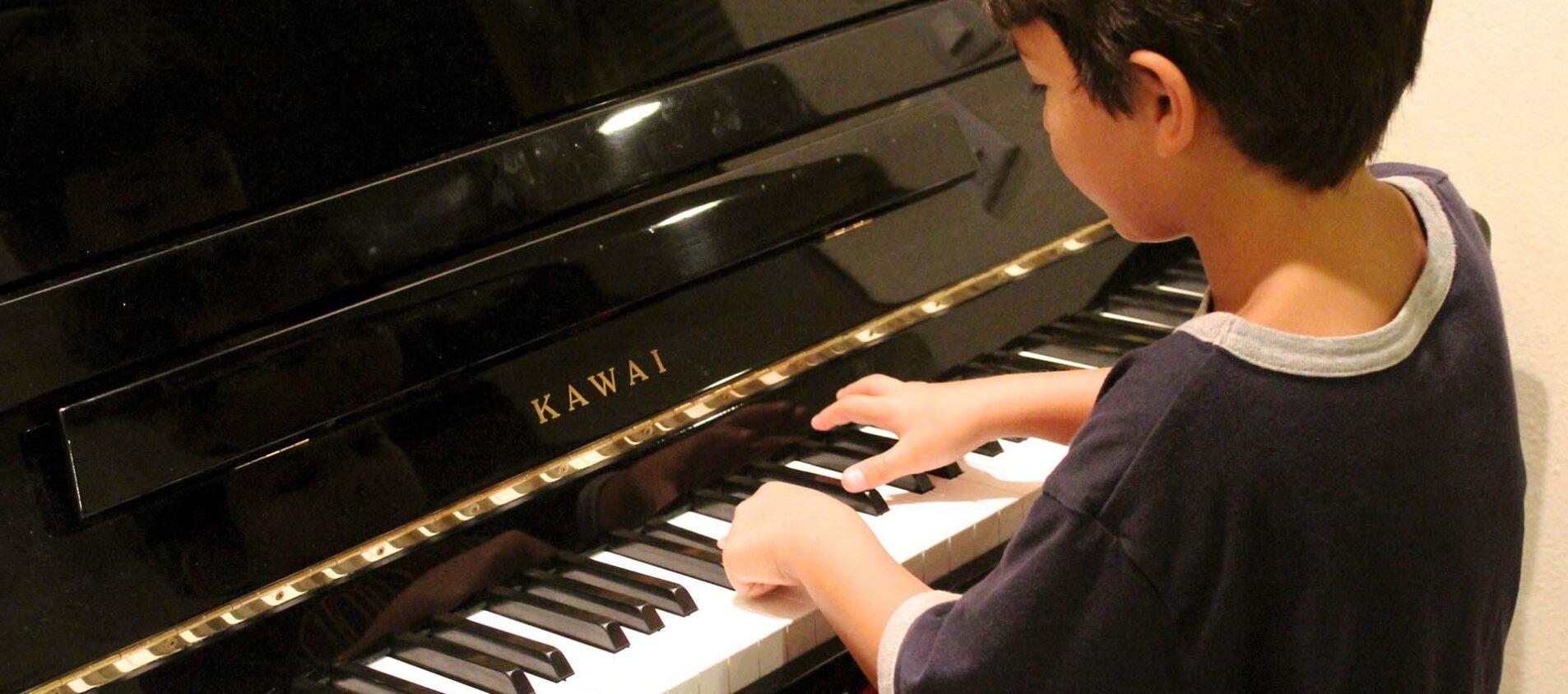 Liten pojke spelar piano.